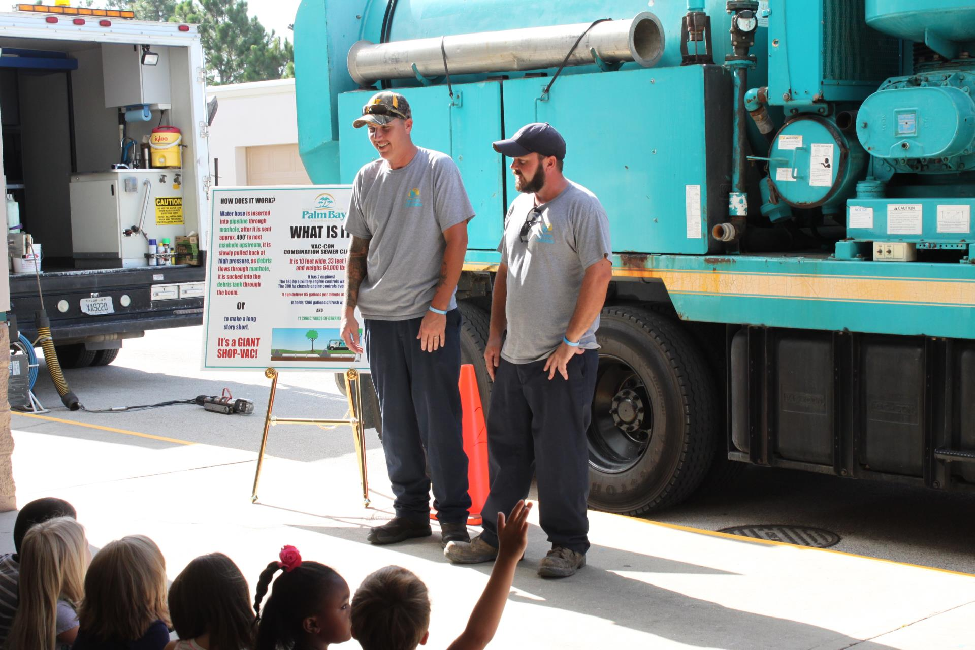 Photo of the Vac-Con truck and technicians explaining the truck to children